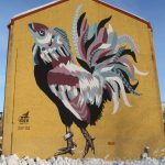 Talon_seinällä_on_maalattu_kalakukko_jolla_on_kalanpää_ja_muu_osa_kukkoa.